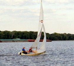 A sailboat (racing dinghy) and barge share the Mississippi River