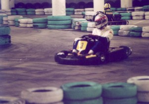 A kart racer takes a turn on an indoor track