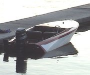"A 1962 ""Rebel"". A wooden speedboat with an outboard engine."