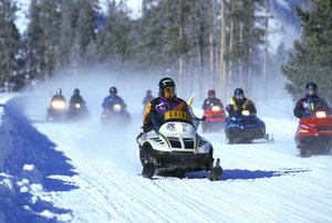 A snowmobile tour at Yellowstone National Park, note the snowdust in the air (NPS Photo)